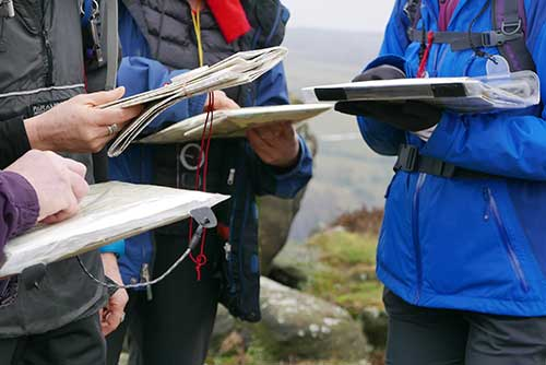A group of walkers practising map and compass skills